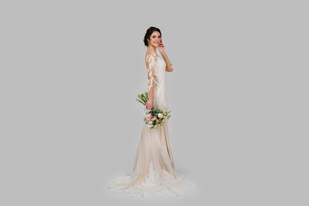 Молодая привлекательная невеста с букетом в современном свадебном образе с короткими рукавами