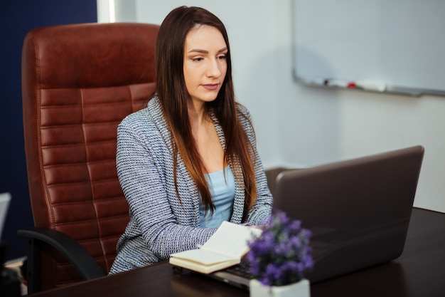 Young attractive brunette caucasian, happy beautiful business woman in in business cardigan suit sits at table in bright office. portrait of businessman, director of organization. woman at work