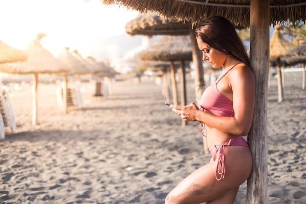 Молодая привлекательная брюнетка женщина использует телефон на пляже под солнцем зонтика во время заката. золотая подсветка и концепция подключенных людей. отдых на курорте на тропическом острове