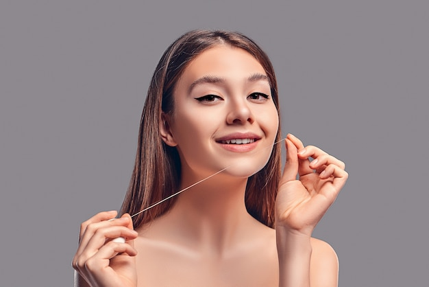 Young attractive brunette girl with loose hair uses dental floss isolated on gray background.