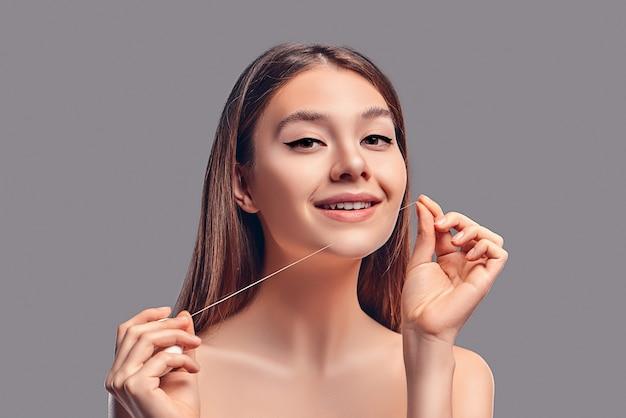 Молодая привлекательная брюнетка девушка с распущенными волосами использует зубную нить, изолированную на сером фоне.