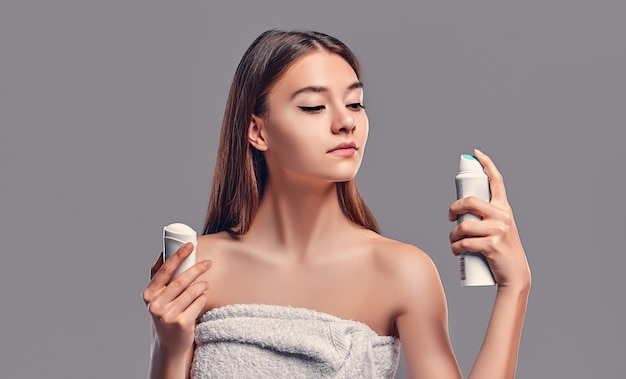 Young attractive brunette girl with loose hair with deodorant stick and antiperspirant aerosol isolated on gray background. body care.