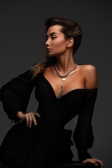 젊은 매력적인 갈색 머리 섹시 한 여자는 에로틱 한 검은 칵테일 드레스의 자에 앉는 다. 회색 배경입니다.