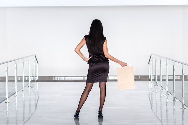 Young attractive brunette woman dressed in a black business suit holding paper shopping bag, walking on mall. back to the camera.
