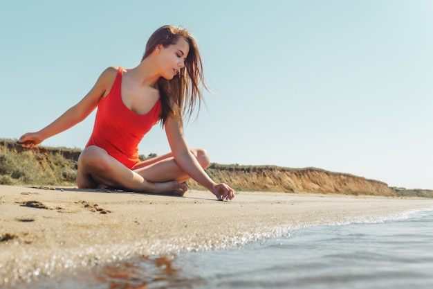 青い空と砂の上を書く赤いボディの若い魅力的なブルネットの女性