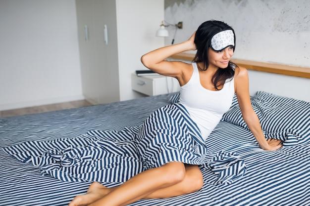 Giovane donna castana attraente che si siede sul letto in pigiama e maschera per dormire, sorridente in camera da letto, emozione felice, pigro al mattino, sveglia, gambe assonnate, sexy, magre