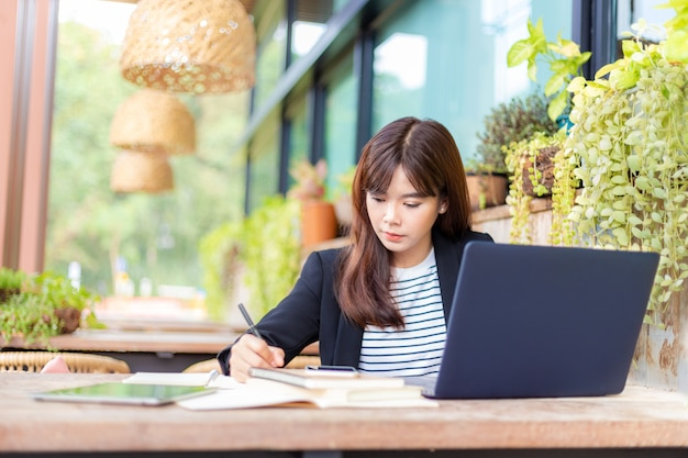 Young attractive business woman in her casual suit working on her computer at outdoor patio of her office, working mobile or young entrepreneur concept