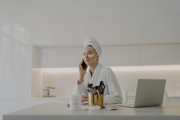 Молодая привлекательная деловая женщина в халате и тюрбане из полотенца на голове с косметическими заплатками под глазами разговаривает по мобильному телефону и работает на ноутбуке, готовясь к работе утром дома