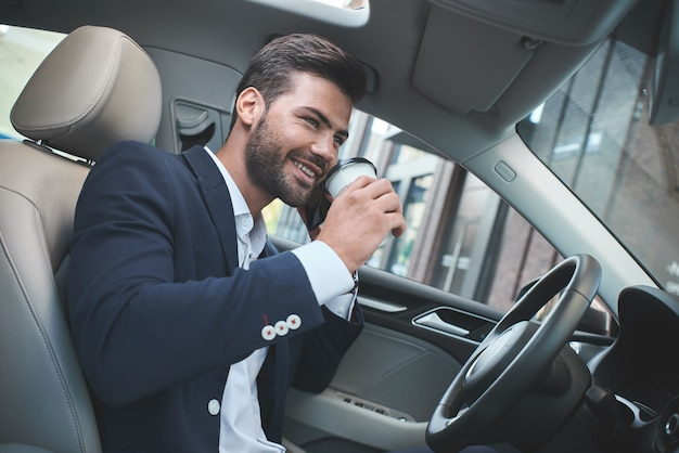 Young attractive businessman in car drink coffee and talking on