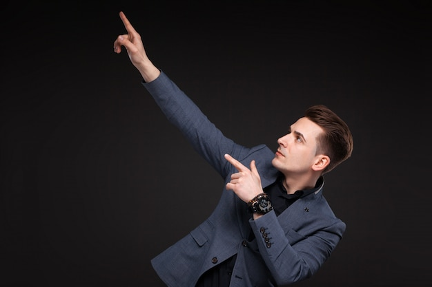 Young attractive businessman in grey jacket, costly watch and black shirt, black background