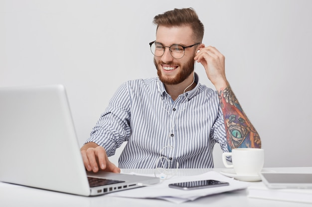 Young attractive businessman has happy expression as rests after hard work, listens to music or watches film with earphones and laptop computer. tattooed hipster student enjoys favourite audio trac
