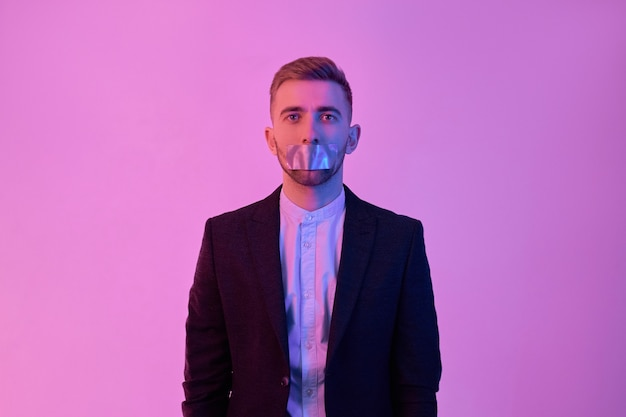 네온 핑크에 고립 된 그의 입에 스카치 테이프와 검은 양복과 흰 셔츠에 젊은 매력적인 사업가