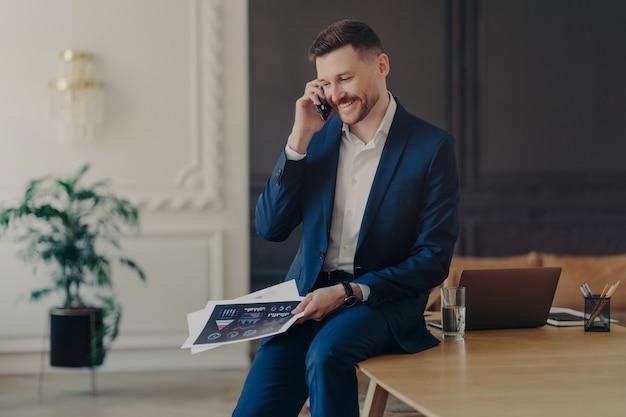 フォーマルなダークブルーのスーツを着た魅力的な若いビジネスマンが、オフィスで電話で話し、ノートパソコン、コップ1杯の水、鉛筆を持って仕事机に座りながら、チームの良い結果を聞いて微笑む