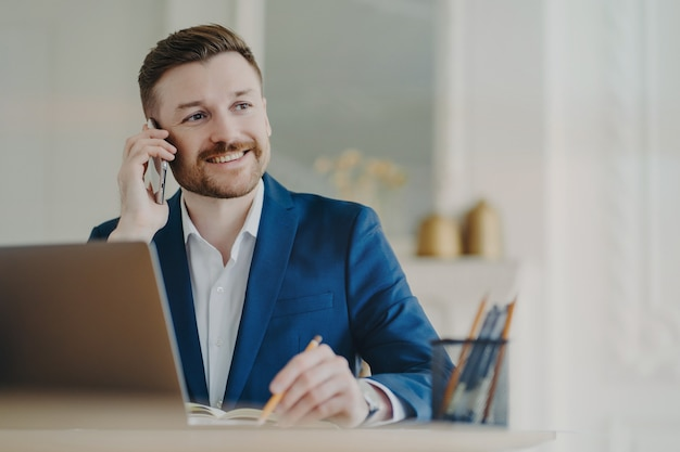 フォーマルスーツを着た若い魅力的なビジネスマンが、パートナーやクライアントと携帯電話で話し、現代のオフィスで働きながら微笑み、鉛筆で良い結果を書き留める