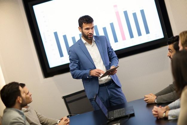Молодой привлекательный бизнесмен, показывающий презентацию своим коллегам в конференц-зале
