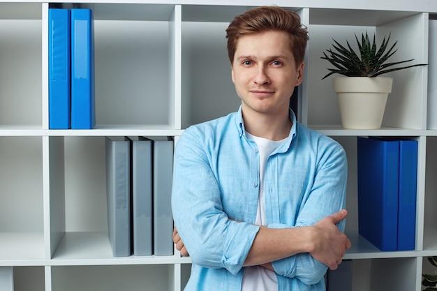 Молодой привлекательный бизнесмен, стоя в офисе со скрещенными руками
