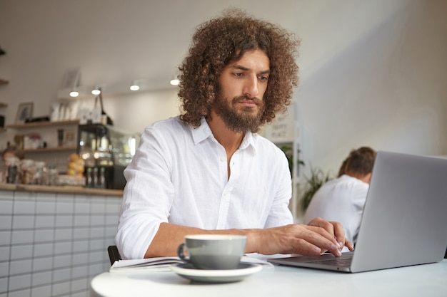 Young attractive businessman with brown curly hair posing over cafe interior, working out of office with modern laptop, looking intently at monitor