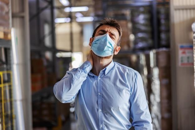 首の痛みを持っていることにフェイスマスクを持つ若い魅力的なビジネスマン。倉庫内部。コロナ発生の概念。