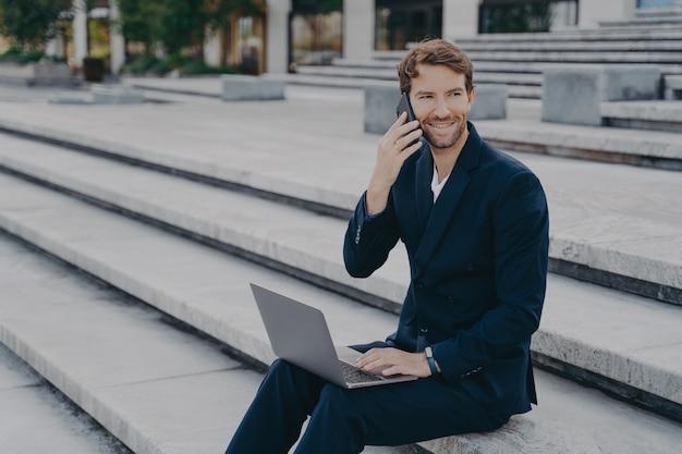 밖에서 스마트폰으로 말하는 노트북 작업을 하는 젊은 매력적인 사업가