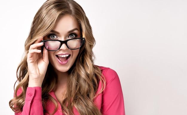 안경을 쓴 매력적인 젊은 여성 사업가는 기쁨과 즐거움의 표현을 보여줍니다