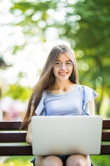Молодая привлекательная бизнес-леди сидит на скамейке в парке и работает над своим ноутбуком