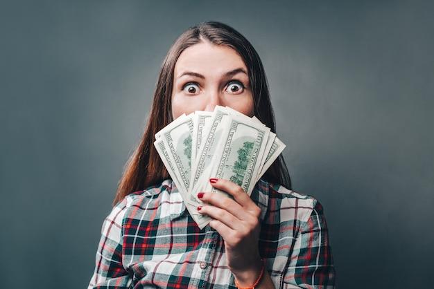 Молодая привлекательная небрежно одетая женщина выглядит потрясенной, держа в руке долларовые банкноты