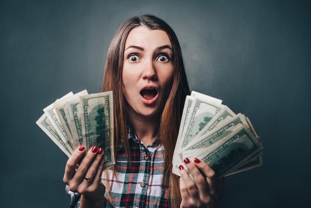 Молодая привлекательная небрежно одетая женщина выглядит потрясенной, держа в руках долларовые банкноты