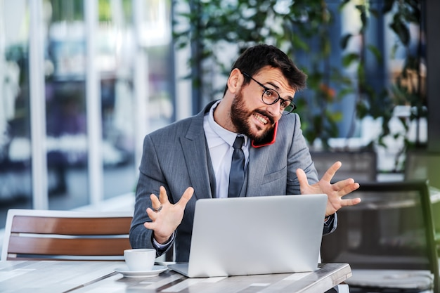 Young attractive caucasian bearded businessman sitting on terrace of cafe, holding smart phone on shoulder and convincing client to have cooperation with him.