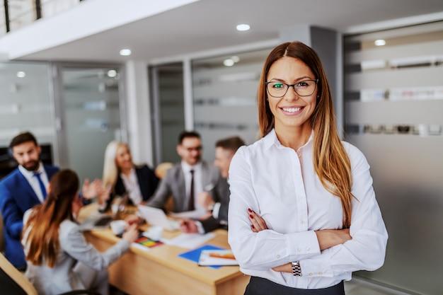 フォーマルな服装で立っている若い魅力的な白人女性実業家の手が交差し、カメラ目線で会議室に立っています。背景には、彼女の同僚がプロジェクトに取り組んでいます。