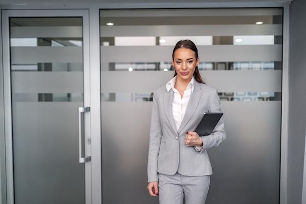 Молодой привлекательной кавказской коммерсантки в формальной одежде стоя перед залом заседаний и держа таблетку в руках. концепция корпоративного бизнеса.