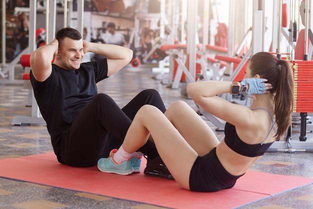ジムで一緒に運動若い魅力的な白人カップル。お互いの前の床に座って、頭の後ろに手を置いて腹筋運動をしている男女に合います。