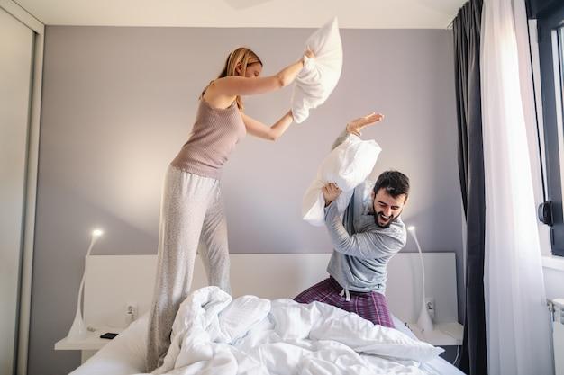 枕を持っている若い魅力的な白人カップルは、朝の寝室で戦います。どちらもパジャマ姿です。