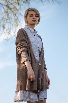 晴れた日に木と青い空の前に立っている斑点のあるドレスとセーターの短い髪の若い魅力的な白人女性