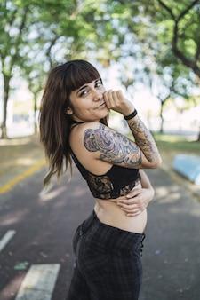 Молодая привлекательная кавказская женщина с татуировками стоит в парке и делает милое лицо