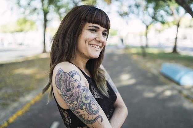 Giovane donna caucasica attraente con tatuaggi in piedi nel parco che fa una faccia carina