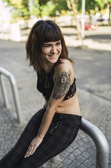 Giovane femmina caucasica attraente con i tatuaggi in strada
