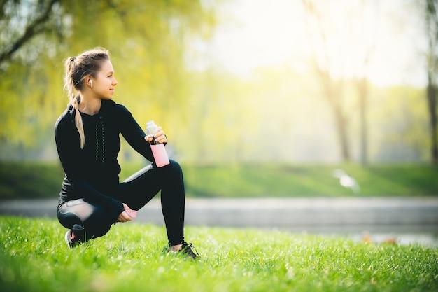 Молодая привлекательная кавказская девушка в спортивном костюме отдыхает после бега в парке, сидит на траве, пьет воду и улыбается, наслаждаясь своими беспроводными наушниками