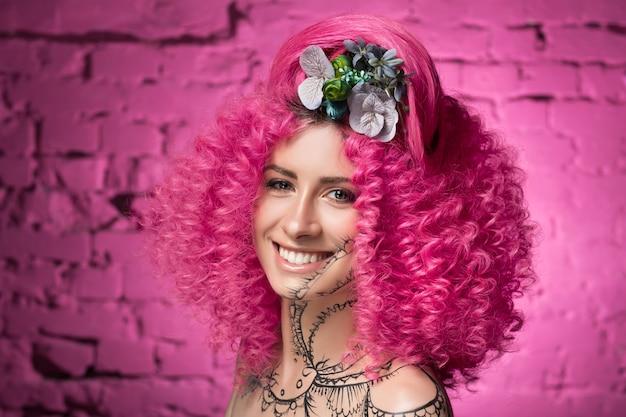 아프리카 스타일 곱슬 밝은 분홍색 머리 문신 얼굴과 목을 가진 젊은 매력적인 백인 여자 모델