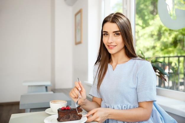 若い、魅力的な、白人、女性、楽しむこと、チョコレート、ケーキ、ホット、コーヒー、現代、コーヒーショップ、正午。