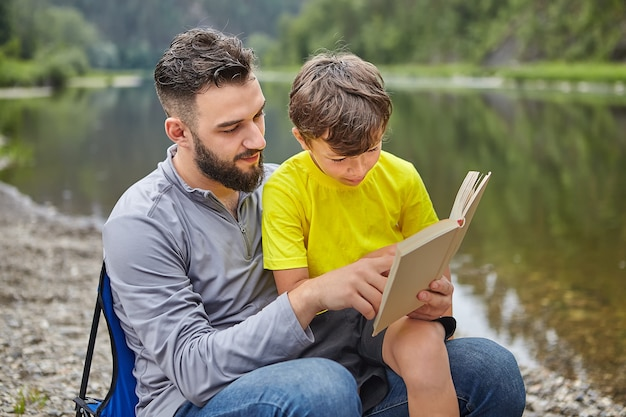 Young attractive caucasian man and his son are sitting on river bank and reading book, eco-tourism.
