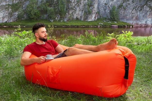 若い魅力的な白人男性は、彼の手にお茶やコーヒーを片手にオレンジ色のエアソファに横たわって、彼の休暇中にリラックスしています。