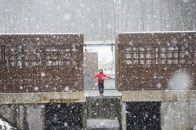 Молодой привлекательный кавказский мужчина в красной куртке стоит на плотине и наслаждается снегопадом