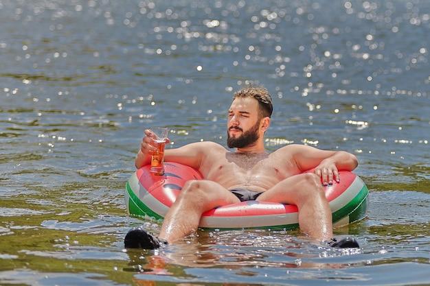 あごひげを生やした若い魅力的な白人男性は、彼の手にガラスを持った膨脹可能なリングで川に沿って漂っています。