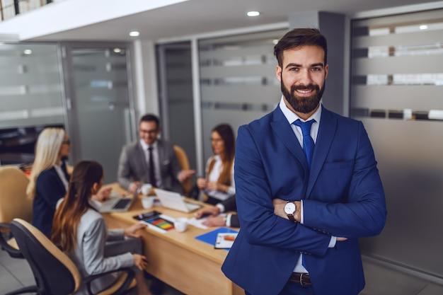 Молодой привлекательный кавказский улыбающийся довольный бизнесмен в костюме, стоя в зале заседаний со скрещенными руками. на заднем плане встреча его коллег.