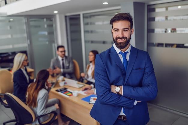 Молодой привлекательный кавказский улыбающийся довольный бизнесмен в костюме, стоящий в зале заседаний со скрещенными руками