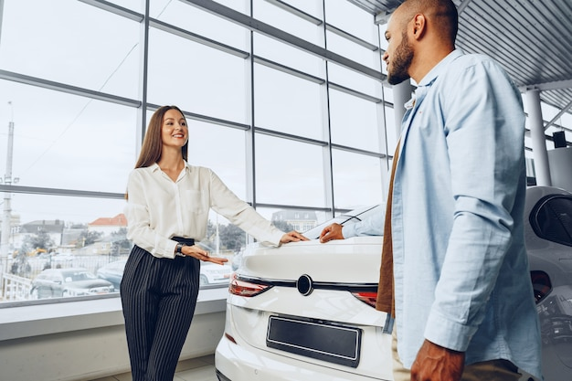 Young attractive caucasian woman salesperson in car showroom showing a car to her male african american client
