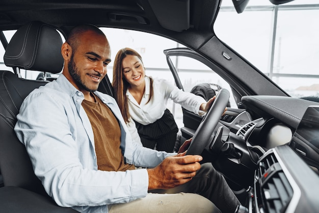 Young attractive caucasian woman salesperson in car showroom