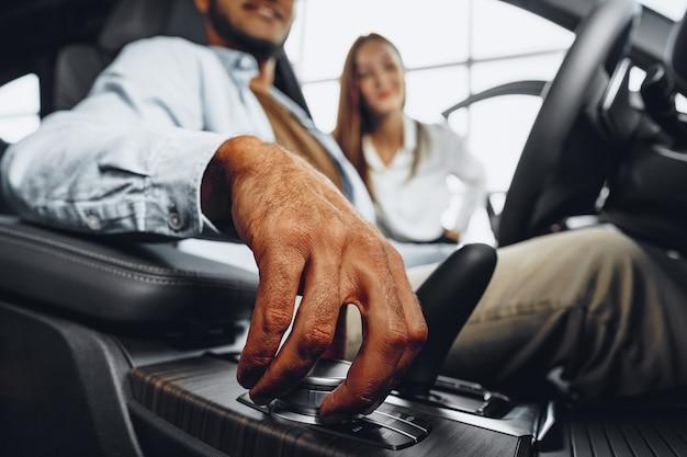 彼女の男性のアフリカ系アメリカ人のクライアントに車を見せて車のショールームで若い魅力的な白人女性の販売員
