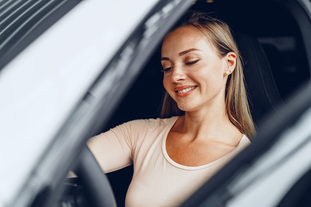 Young attractive caucasian woman sits in her newly bought car in dealership