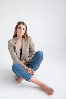 スタジオでスーツのジャケットの長い茶色の髪を持つ若い魅力的な白人女性